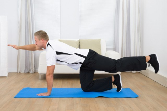 man performing bird-dog ab exercise on a gym mat at home