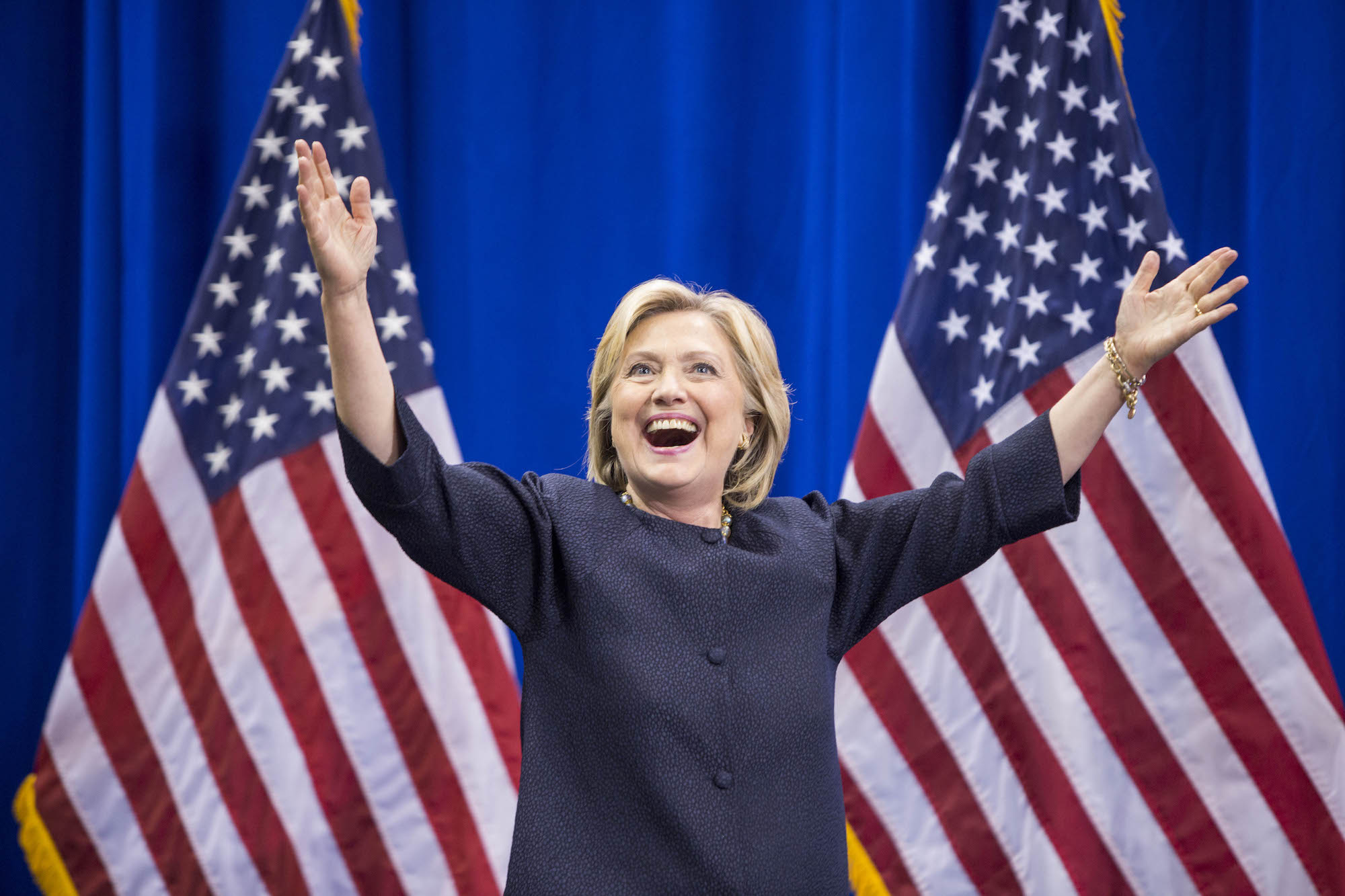 Democratic presidential candidate Hillary Clinton raises her arms stands on stage as voters prepare to vote for Democrats or Republicans