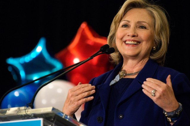 Hillary Clinton giving a speech into a microphone in front of red, white, and blue stars and balloons