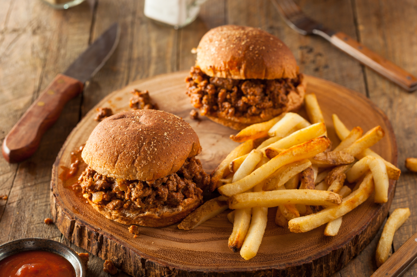 two sloppy joe sandwiches on buns with a pile of french fries