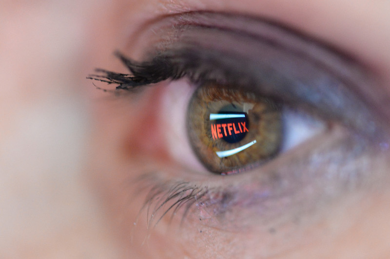 The Netflix logo reflected in the eye of a user