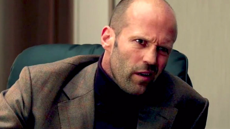 Jason Statham sitting in a chair making a funny face in Spy