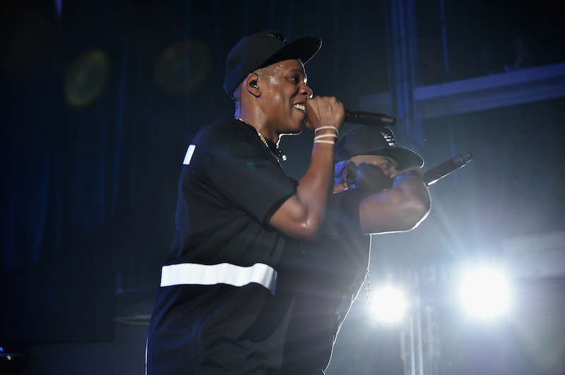 JAY-Z holds up a microphone on stage