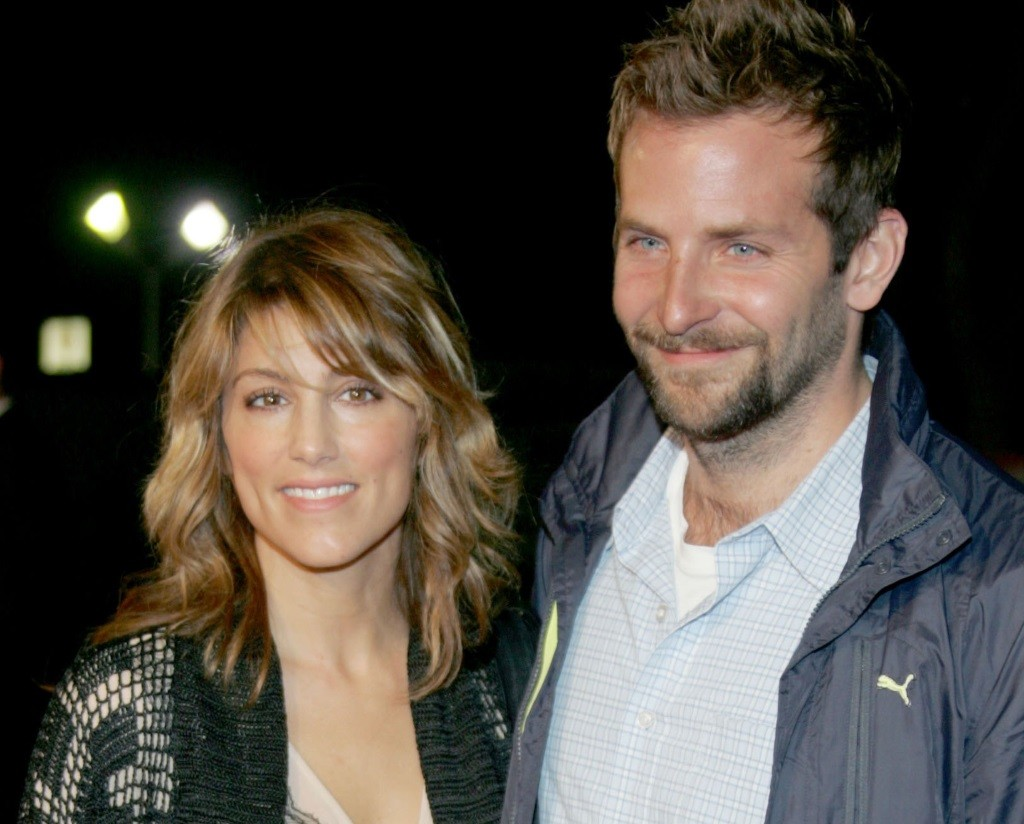 Bradley Cooper with his arm around Jennifer Esposito, while they both smile for the camera