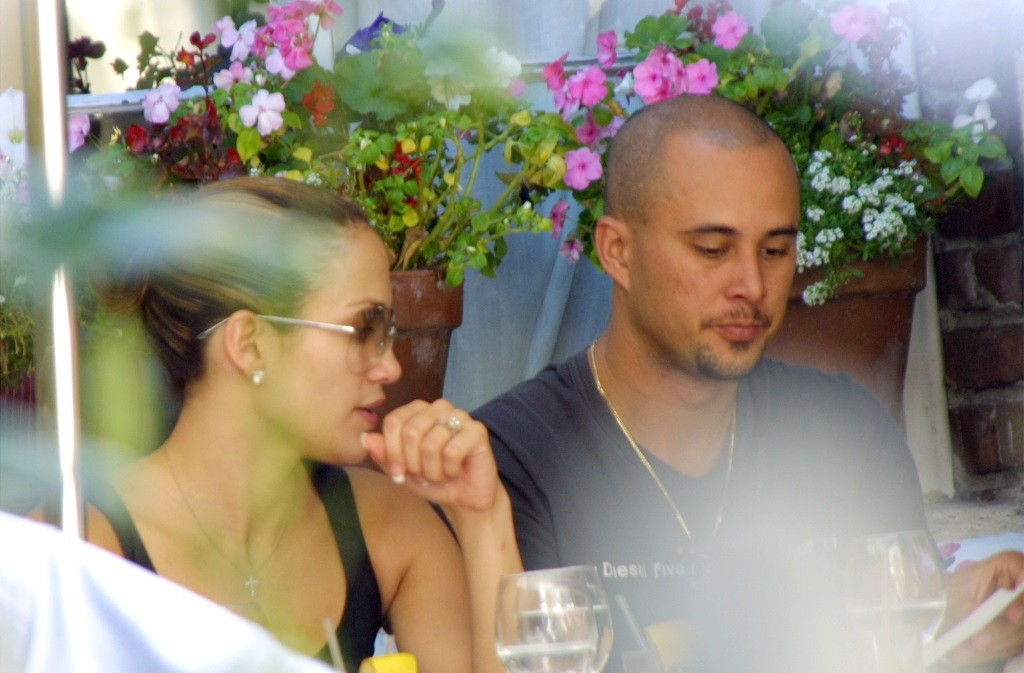 Jennifer Lopez and Cris Judd sitting next to each other at an outdoor restaurant in a paparazzi photo