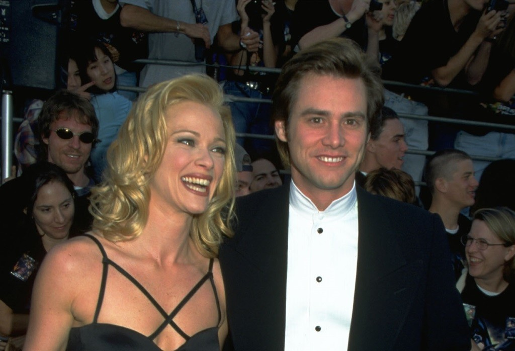 Lauren Holly and Jim Carrey on the red carpet, smiling and looking at the camera