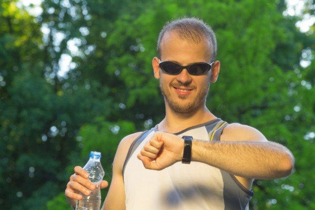 young man checking time on his wrist watch after running