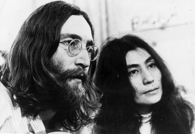 John Lennon and Yoko Ono standing next to each other and looking in the same direction.