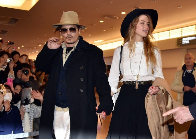 Johnny Depp arrives at an airport in Tokyo with Amber Heard.