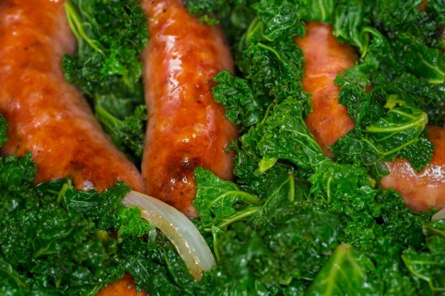 sloce up of kale cooked with onion and sausage