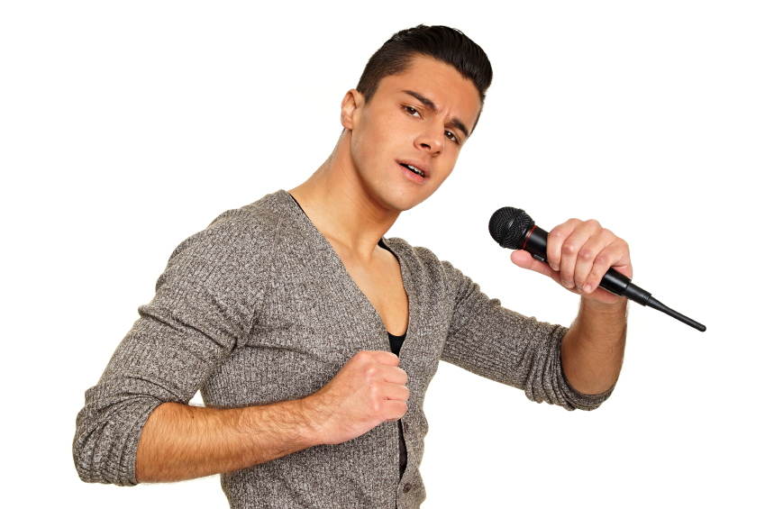 young man posing and singing on a microphone