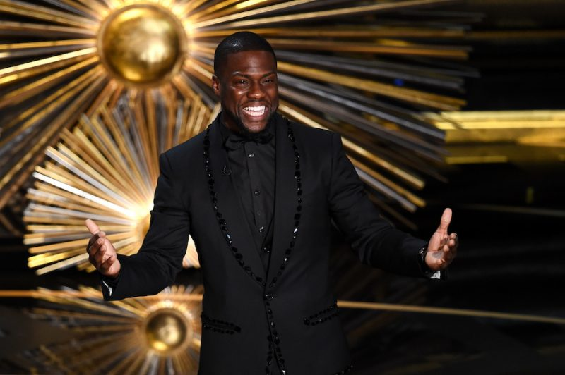 Kevin Hart smiles and holds his hands out while on stage