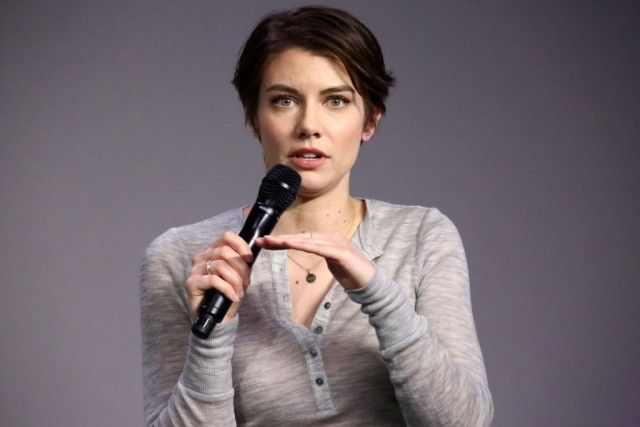 Lauren Cohan speaking into a black microphone while gesturing with her hands.