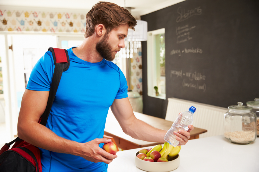 Man wearing gym clothes and a gym bag grabs fruit and a bottle of water for after his workout