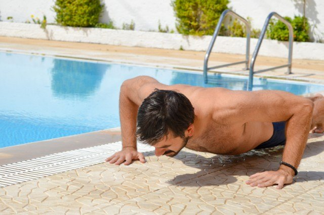 man performs push-ups next to the pool