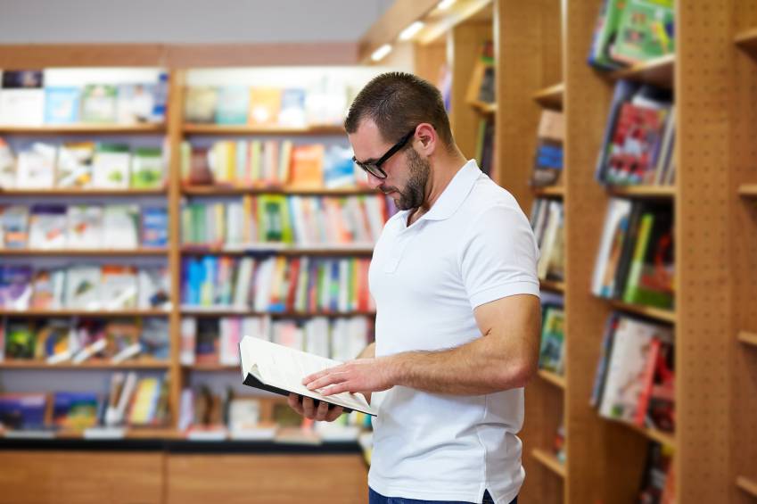 young man standing and reading a book in the library