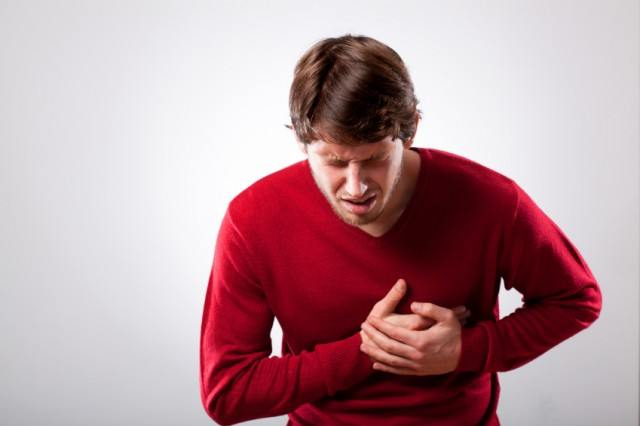 man holding his chest in pain