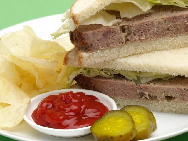 close up of a meatloaf sandwich with ketchup and pickles