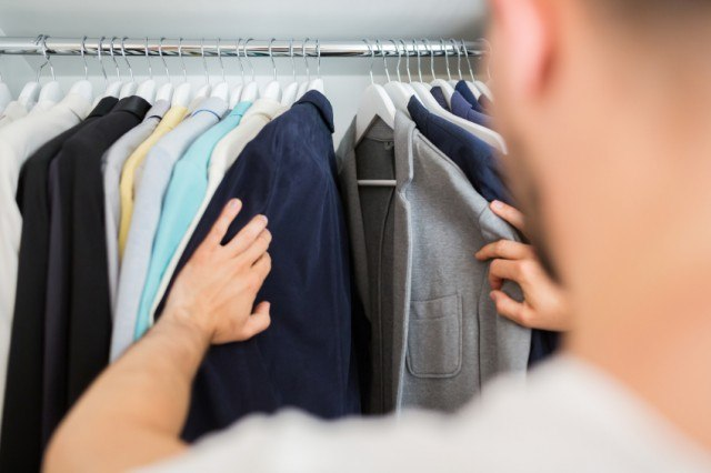 man choosing clothes from his closet