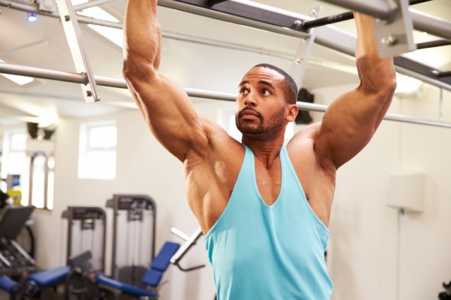 muscular man working out at the gym using monkey bars
