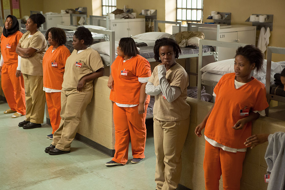 Inmates are lined up outside of their bunks.