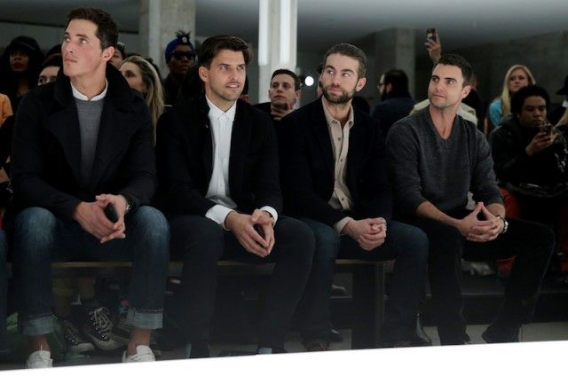 men wearing layered clothes and watching a show