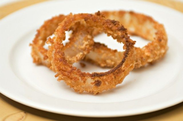 close up of onion rings on white plate