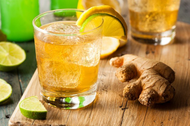 Ginger Ale Soda with ginger on a wooden board