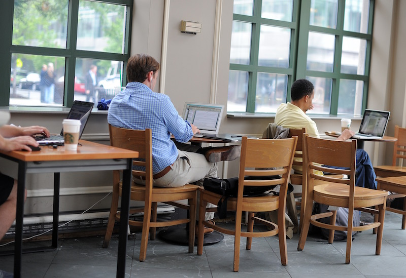 People use their laptops at a Starbucks that offers free WiFi