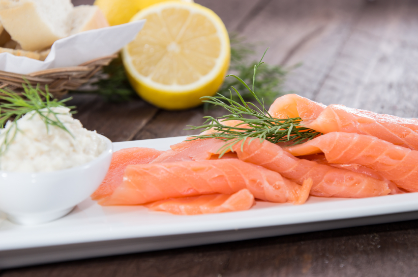 fresh Salmon in a white tray with lemon in the background