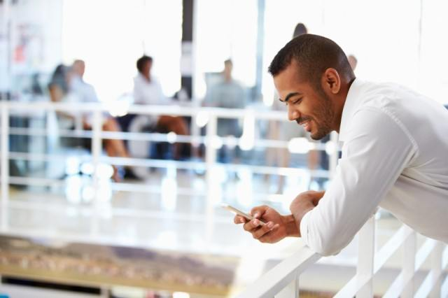 Man holding smartphone while texting and smiling
