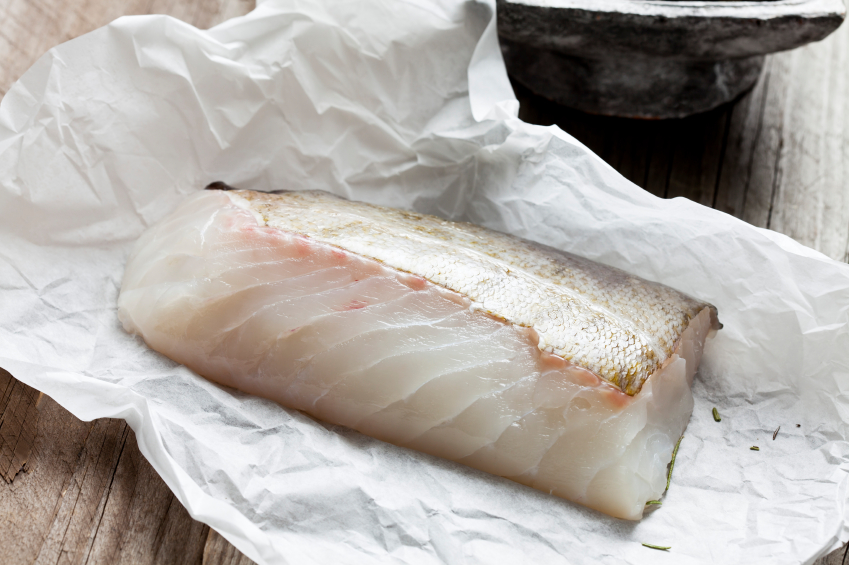 raw cod fish fillet on a piece of parchment paper