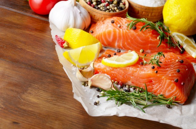 parchment paper with raw salmon, lemons, garlic, herbs, and whole peppercorns