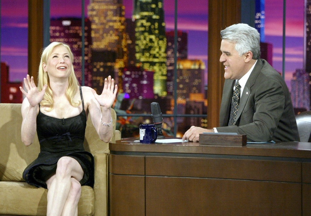 Renee Zelwegger with his hands out, talking to a smiling Jay Leno on TV