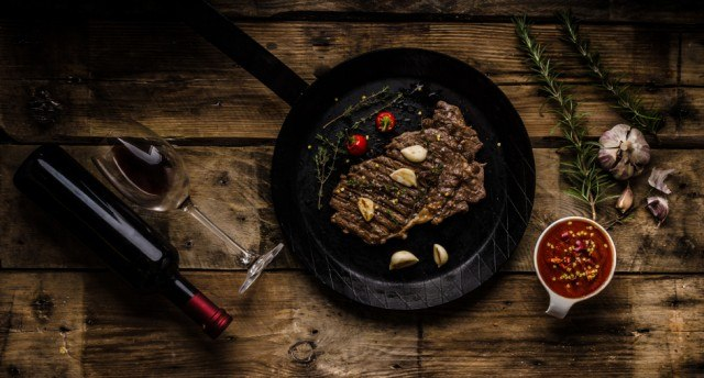 rib eye steak in a cast-iron skillet with a bottle of wine
