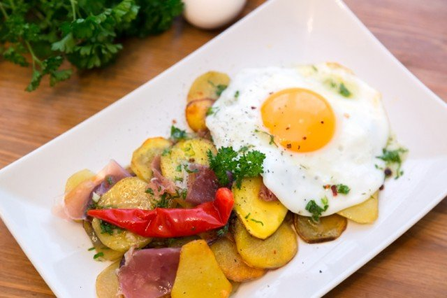 raosted potato coins and ham topped with a sunny side-up egg and a chile pepper