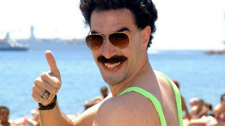 Sacha Baron Cohen posing on a beach in sunglasses and a green swim suit giving a thumbs up in Borat