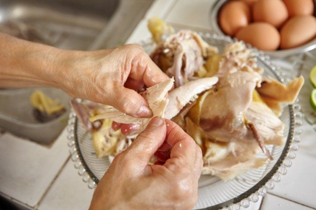 using hands to shred cooked chicken
