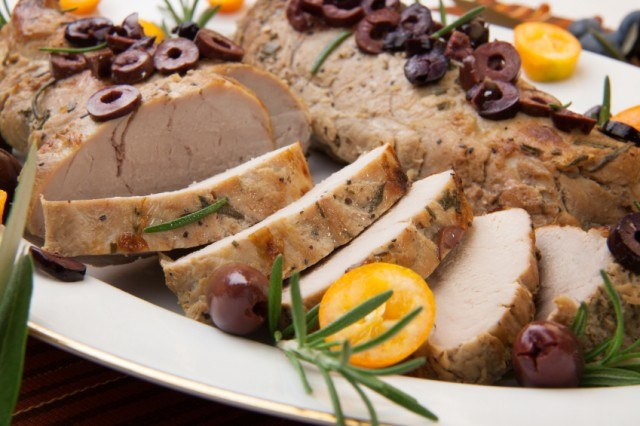 sliced roast pork tenderloin with olives, kumquats, and rosemary