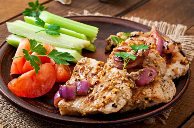pork chops with mustard and red onion sauce with a side of raw vegetables