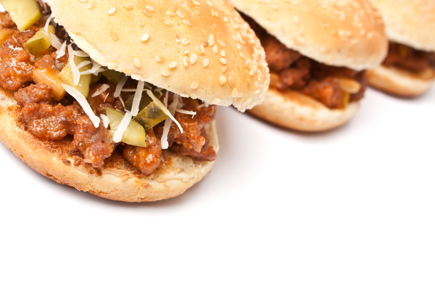 three sloppy Joes with shredded cabbage and pickles