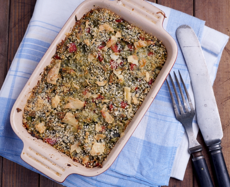 Spinach casserole in a dish with fork and knife