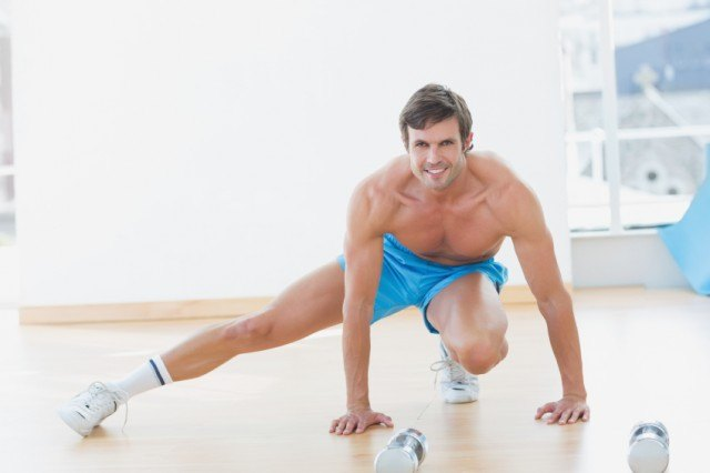shirtless man lunges to the side with hands on the floor