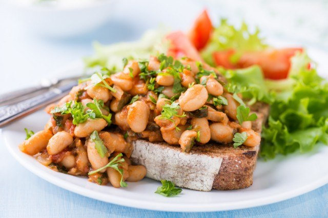 Stewed white beans in tomato sauce on hearty toast with fresh herbs