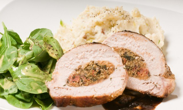 Pork Roast With A Savory Filling Served With Potatoes And Green Vegetables