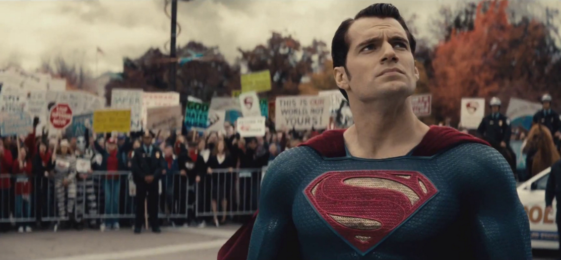 Henry Cavill as Superman with a crowd of picketers behind him