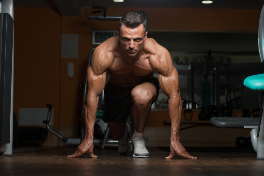 muscular man at the gym kneeling on one leg with his hands on the ground