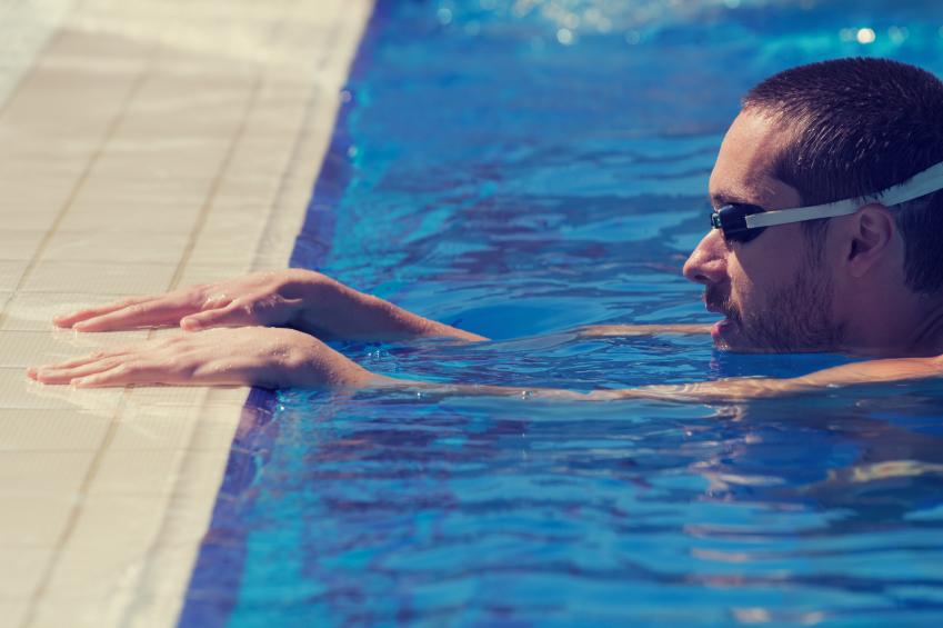 man wearing goggles rest at the edge of a pool