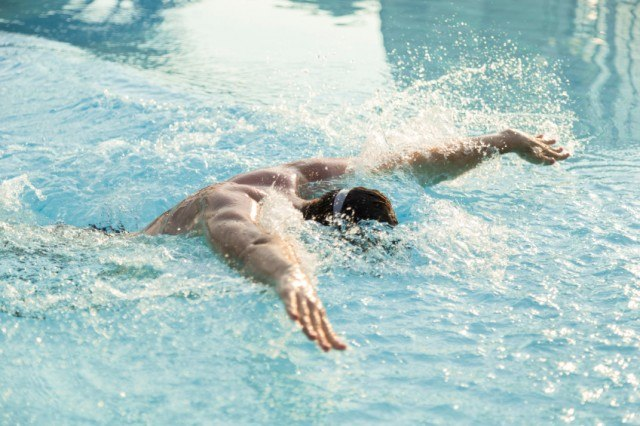 man swimming butterfly stroke in a pool