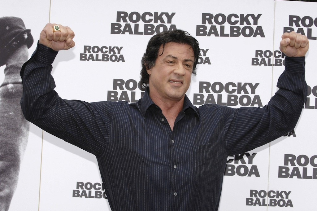 Sylvester Stallone flexes both arms.